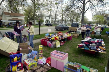 041181ED Melanie Maxwell/The Saginaw News     (L to R) Bargain hunters Stefanie R. Huch, 30, and her mother Connie M. Royle, with Huch's children Colin W., 1, and Madelynn G., 3, all of Spring Lake,  look for cheap buys at one of the many garage sales lining the streets of Freeland  Friday afternoon.  The Freeland Walleye Festival kicks off Saturday with 140 garage sales, walleye fishing and a carnival set up at Pat's Food Center located on Midland Rd.